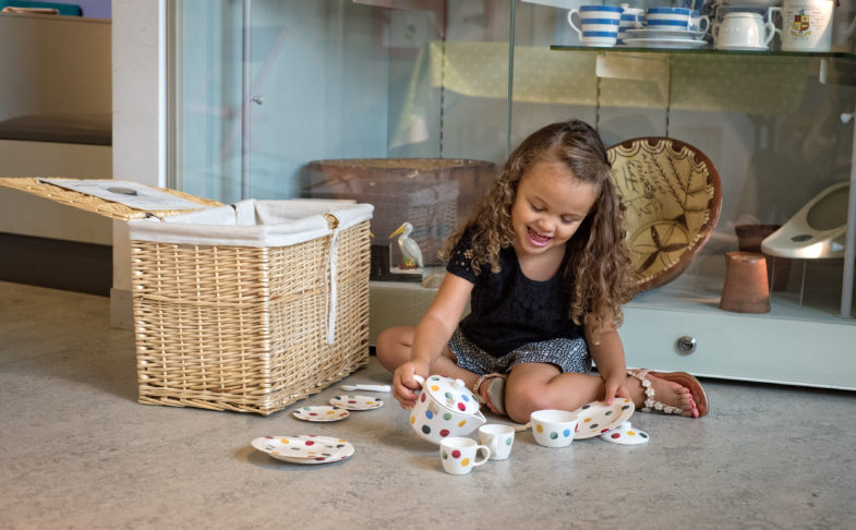 Young girl playing with a tea set at Toddler Tuesdays
