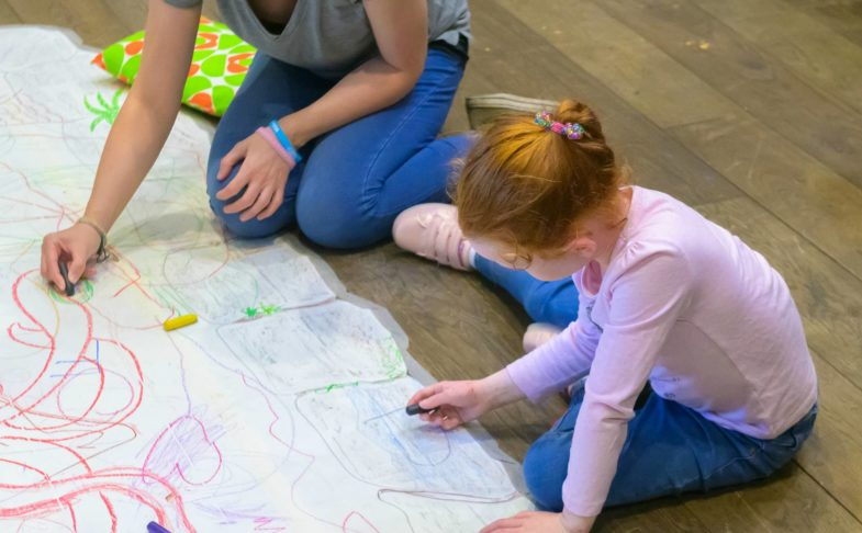 Adult and child drawing on the floor during the Family Weekend event