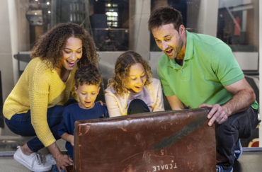 A family looked amazed as they open a large chest in Story Seekers