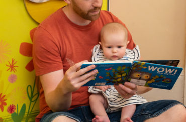Man reading to baby in Wow said the Owl exhibition