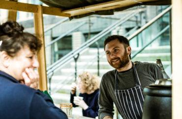 A trader and a customer enjoy a lauch at The Good Market at Sadler's Yard